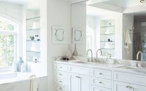 gorgeous bathroom features a white dual washstand topped with gray and white marble under a full length mirror rc studio bathtub alcove with shelves