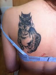 татуировка на лопатке у девушки в виде двух рысей татуировки