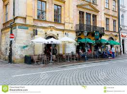 Krakow poland may 25 2017 outdoor seating restaurants at a cobbled street this is visible in front of the historic building at the small market square