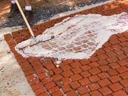 stone patio installation: brush mortar over stones and press between joints