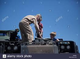 Lance Cpl. Chad Robbins, amphibious assualt vehicle crewman, 3rd Assault  Amphibian Battalion, shows children the driver's