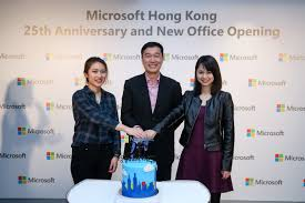 microsoft office company. mr. horace chow, general manager of microsoft hong kong cuts the cake with two office company e