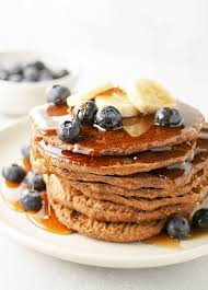 stack of baked buckwheat banana pancakes with blueberries bananas and syrup on top