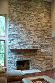 stylish floor to ceiling stone veneer fireplace design with wooden mantel shelf