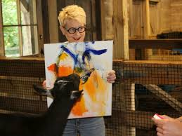 carrie hoffman holds on tight while a nigerian dwarf goat puts the finishing touches on his painting during a behind the scenes tour at the cincinnati zoo