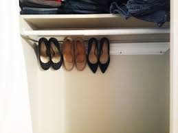 three pairs of high heels hanging on crown molding