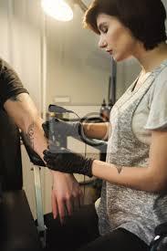Fototapeta Mladá žena Tetování Robí Tetování Na Mužské Rameno
