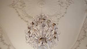 a vintage chandelier on white ceiling in old castle stock