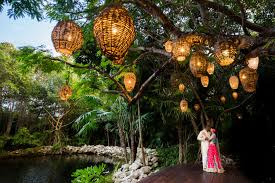 lanterns hanging from trees le light curtains and outdoor chandeliers are just some of the lighting trends we ve seen at destination weddings