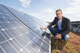 Germany, Munich, Man touching solar ...