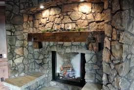 raw mountain stone fireplace wall with rustic wood fireplace mantel and modern gas fireplace