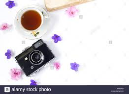 top view of old retro camera and old book on white background with pink flowers and cup of coffee or tea