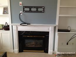 tv wall mount installation with wire concealment over mounting flat screen tv above brick fireplace