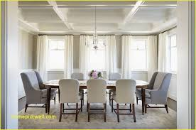 transitional dining room featuring a long oval wood dining table surrounded by upholstered light gray oval