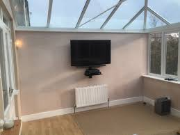 49 lg tv wall mounted on tilting down wall bracket sound bar mounted beneath with av glass shelf virgin and ps4 located on glass shelf