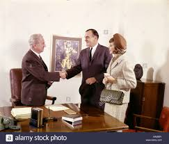 couple standing at desk with executive men shaking hands indoor man woman three bank loan