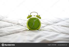 alarm clock on bed in morning with sun light greenery soft and select focus photo by freebird7977