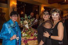 l r mary fromberg poses with one of the 15 spectacular gift baskets she created for the pathfinders mardi gras ball s silent auction together with