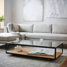 a black frame coffee table with a glass and a wooden top allows storage and looks