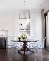 kartell host chairs surround brown round traditional dining table placed beneath a white fringe chandelier
