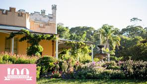 A view of the side of Vaucluse House Estate surrounded by shrubbery and  flowers, and