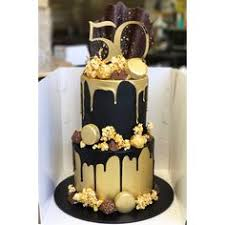 black and gold two tier with caramel popcorn macarons chocolate drip and custom cake topper