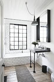 this bathroom uses farmhouse white with subway tile and wood floors but makes it more modern black grout industrialretro lighting simple mirror light grey shower s76 grey