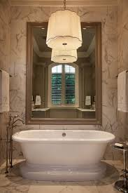 tiled walls framing an oversize taupe mirror over the freestanding pedestal tub with floor mount tub filler faucet below a barbara barry simple scallop