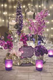 With fairy light walls, the light from this wedding illuminated an  assortment of purple florals on exquisite silver pintuck tablecloths. Silver  cha
