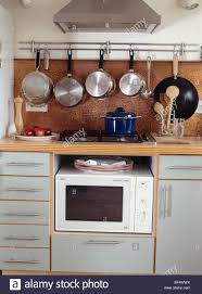 Small Fitted Kitchen Saucepans On Rack Above Hob And Microwave Oven In Gray Fitted