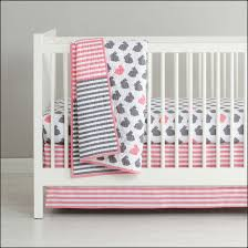 white minimalist land of nod mini crib bedding with pink bed sheets