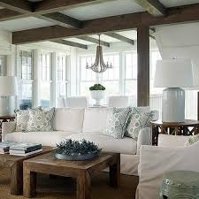 off white slipcovered sofa with side by side wood coffee tables