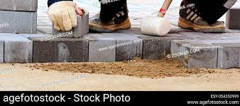 laying paving slab stock photos and