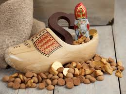 a wooden shoe filled with saint nicholas delicacies such as choclate letters pepernuts spicy