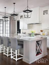 brilliant kitchen features three small cornice hanging lanterns illuminating a long gray wash kitchen island topped with granite countertops ed with