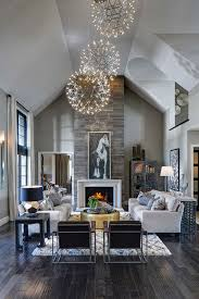 Light contemporary great room / living room with dark rustic wood floors,  stone fireplace and orb chandeliers