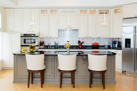 The grey of this kitchen island contrasts the bright white of the cupboards  while the backsplash