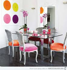 a round glass top table combine with colorful wooden chairs