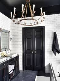 gold finished chandelier with dark colored doors and black ceiling paint for elegant traditional bathroom design