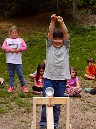 henry key celebrates as his water balloon hits the target in the garden montessori school catapult challenge