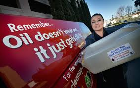 alexandra solano used program recycling specialist for anaheim fire rescue holds a motor oil recycling container given out to anaheim residents at no