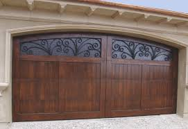 a beautiful wooden garage door with a dark stain has two large windows at the top