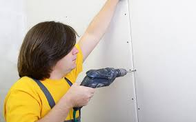 person using a drill to attach two sheets of drywall together
