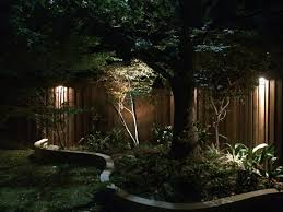 dallas landscape lighting uses downlights mounted high up on fences and walls to create ethereal columns