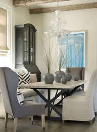 transitional dining room with x based dining table natural linen slipper chairs and gray wingback captain dining chairs interior design by beth webb