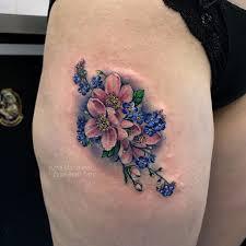 фото небольшой женской татуировки на бедре цветочки в стиле реализм