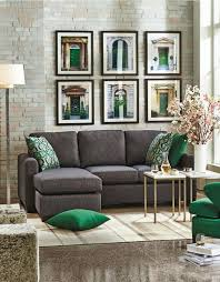 charcoal grey sofa grey stone floors and emerald and gold details for a chic and