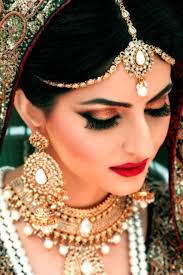 south asian bridal makeup smokey eye with lashes and a red lip desi jewelry