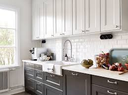 Black And White Kitchen With White Top Cabinets And Black Bottom Cabinets  Paired With White Countertops