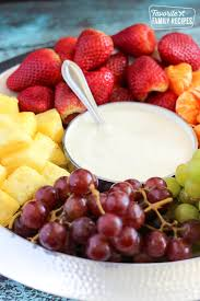 easy fruit dip in a bowl surrounded by strawberries oranges pineapples red gs
